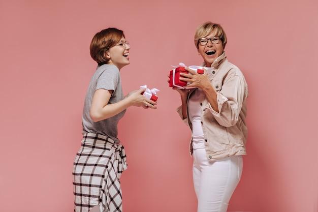 Alegres duas senhoras de cabelos curtos com óculos legais em roupas elegantes, rindo e segurando caixas de presente vermelhas sobre fundo rosa.