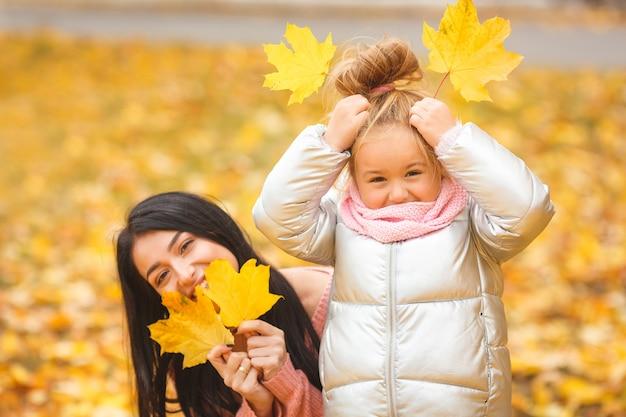 Alegres garotas brincando com folhas amarelas. mãe feliz e criança pequena no outono se divertindo