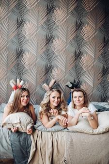 Alegres garotas caucasianas deitadas na cama, curtindo suas vidas e sorrindo no grande quarto luminoso