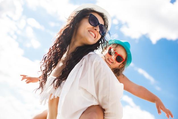 Alegres garotas na praia se divertindo. jovem mãe e sua filha bonita no litoral.