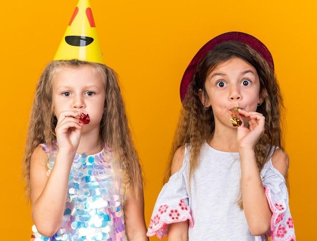 Alegres garotinhas bonitas com chapéus de festa soprando apitos isolados em uma parede laranja com espaço de cópia