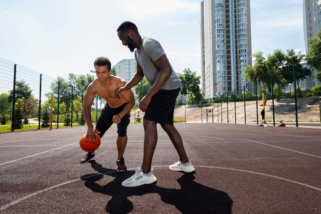 Alegres homens treinando na quadra de basquete