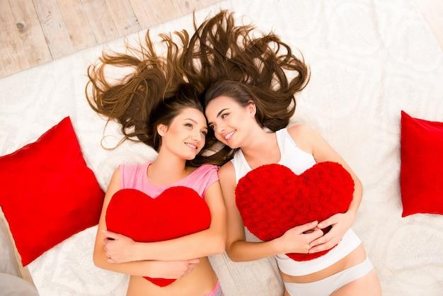 Alegres lindas garotas de pijama deitada na cama segurando travesseiros