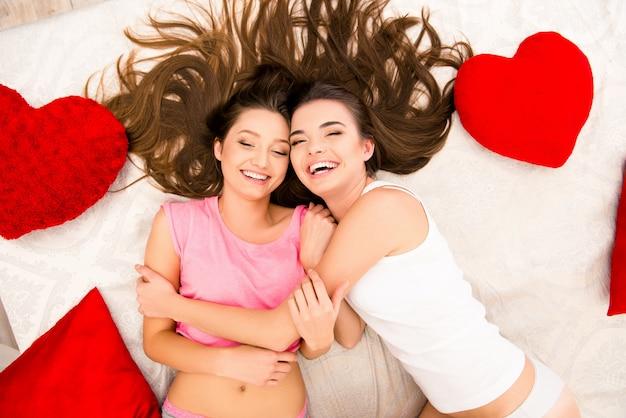Alegres lindas garotas de pijama deitadas na cama se abraçando