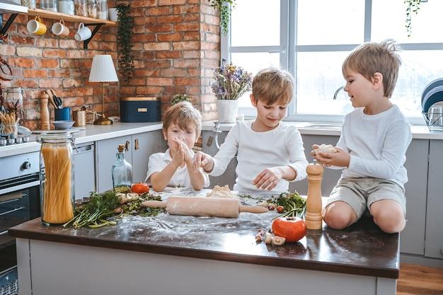 Alegres meninos na cozinha cozinham pizza usando equipamento de cozinha, preparando legumes com massa.