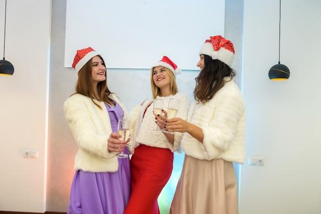 Alegres três mulheres com taças de champanhe, posando na festa. celebração de ano novo e natal