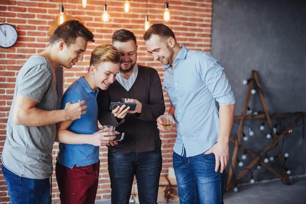 Alegres velhos amigos se comunicam e telefonam para o relógio, copos de uísque no pub. estilo de vida de entretenimento. wifi pessoas conectadas na reunião de mesa de bar