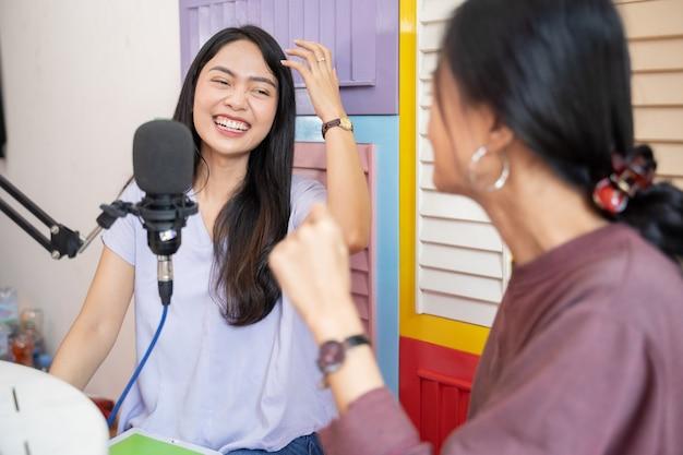 Alegria de duas garotas rindo enquanto conversam em um programa de podcast usando o microfone