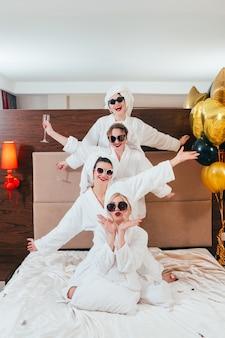 Alegria e diversão da festa de despedida. decoração de balões. linha de posar mulheres sorridentes em óculos de sol, roupões de banho e turbantes de toalha.