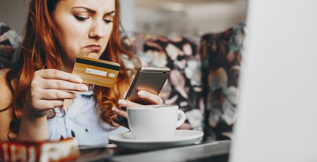 Além disso, o tamanho feminino mão olhando para a tela do smartphone enquanto segura um cartão de crédito, fazendo uma transação online, enquanto está sentado em uma cafeteria.