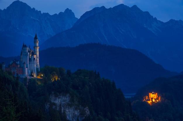 Alemanha. noite de verão na baviera. luzes de dois castelos: neuschwanstein e hohenschwangau tendo como pano de fundo montanhas arborizadas