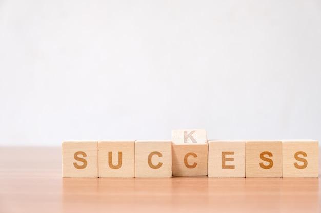 Aleta a letra em mudança no bloco de madeira da sucção ao conceito do sucesso para a melhoria a com sucesso.