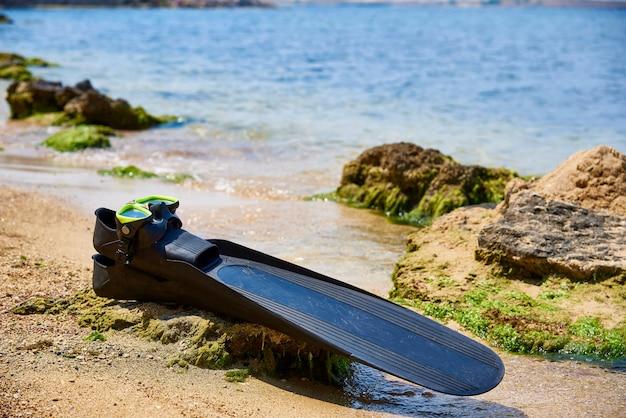 Aletas e máscara subaquáticas na praia na luz solar.