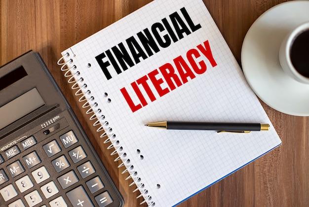 Alfabetização financeira escrita em um bloco de notas branco perto de uma calculadora e uma xícara de café em uma superfície de madeira escura