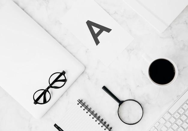 Alfabeto a no papel; lupas; diário; xícara de café; tablet digital; teclado sobre o pano de fundo texturizado