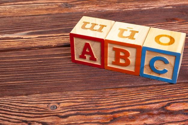 Alfabeto de bloco de madeira deitar no chão de madeira