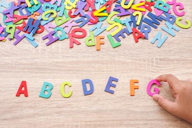 Alfabeto de madeira colorido e mão tipo g. vista superior no fundo da mesa de madeira cinza