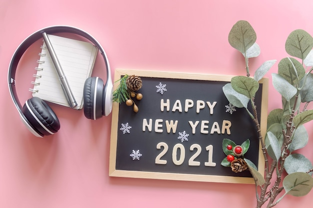 Alfabeto de madeira no quadro de letras de madeira em palavras feliz ano novo 2021, folha, floco de neve e fone de ouvido na configuração plana vista superior. conceito de saudações de temporada de ano novo.