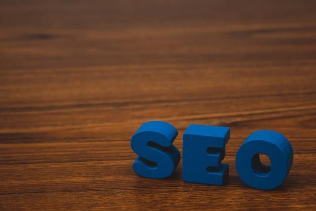 Alfabeto do texto de seo para o conceito da otimização do search engine na tabela de funcionamento de madeira, ideia de seo do negócio.