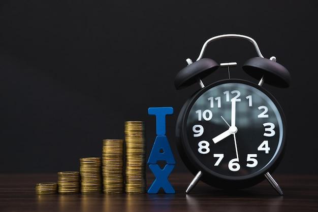 Alfabeto fiscal com pilha de moedas e despertador vintage