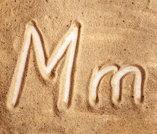 Alfabeto manuscrito inglês letra m na areia