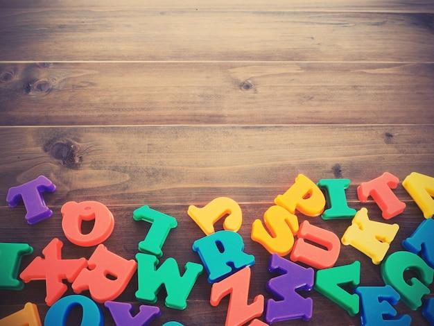 Alfabetos de plástico coloridos na mesa de madeira