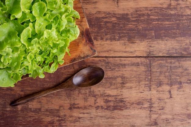 Alface colocada sobre um piso de madeira marrom.
