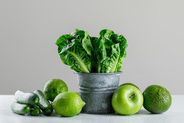Alface com pepino, limão, maçã, abacate em um mini balde na mesa branca e cinza