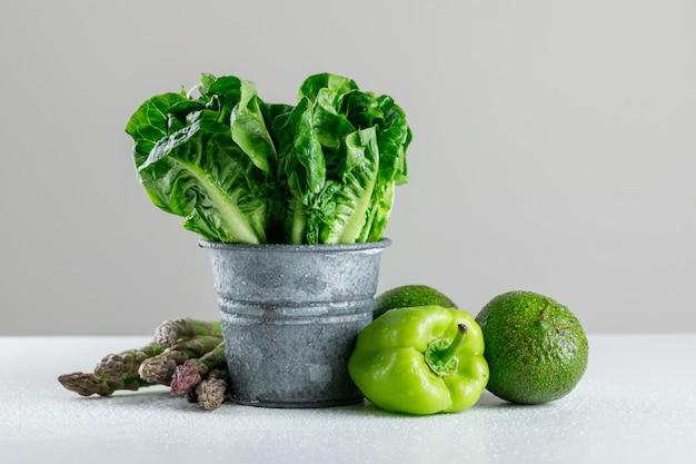 Alface em um mini balde com aspargos, pimenta, abacate na mesa branca e cinza
