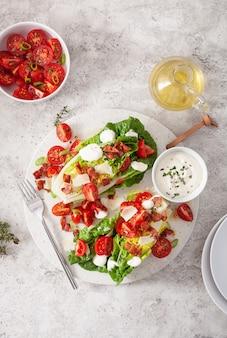 Alface romana coberta com bacon tomate parmesão, molho. almoço saudável da dieta do keto paleo