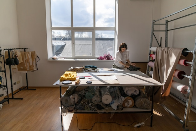 Alfaiataria feminina trabalho com tecido em estúdio jovem designer de roupas medida pano para nova coleção