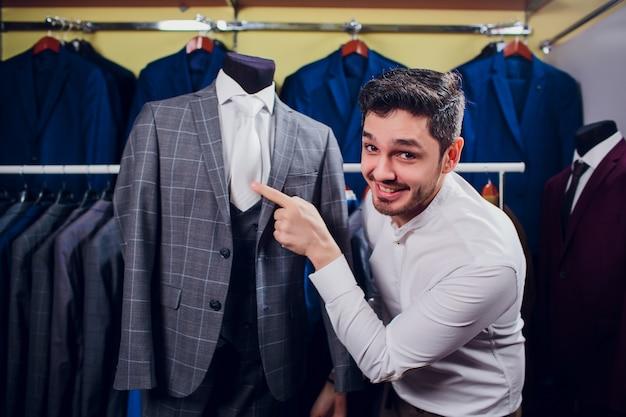 Alfaiate, alfaiataria. terno masculino, alfaiate em sua oficina. ternos de homem elegante pendurado na linha. ternos clássicos de luxo para homens na prateleira na elegante boutique masculina.