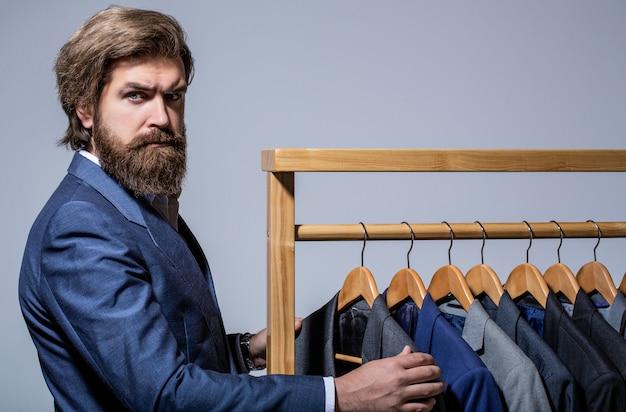 Alfaiate, alfaiataria. terno masculino elegante. oficina. homem bonito barbudo da moda
