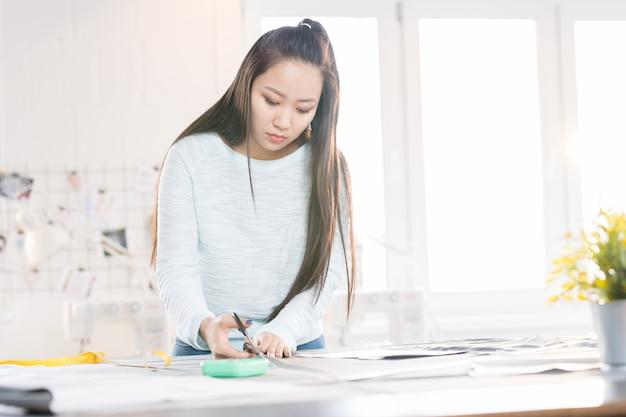 Alfaiate asiático feminino no atelier
