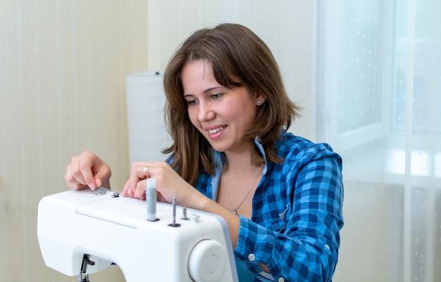 Alfaiate com uma camisa xadrez azul enfia linha em uma máquina de costura em sua oficina.