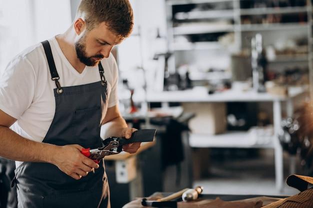 Alfaiate de homem trabalhando com tecido de couro