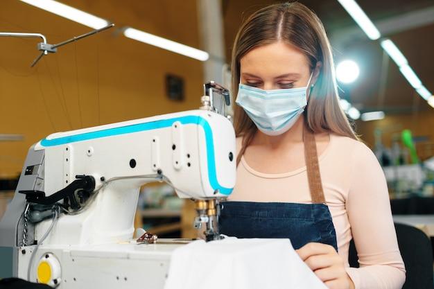 Alfaiate de jovem mulher caucasiana, trabalhando na fábrica de costura, usando máscara médica protetora