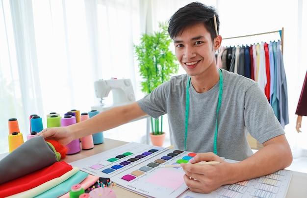 Alfaiate étnico alegre emoção feliz e positiva sentado à mesa com amostras de tecido e vestuário.