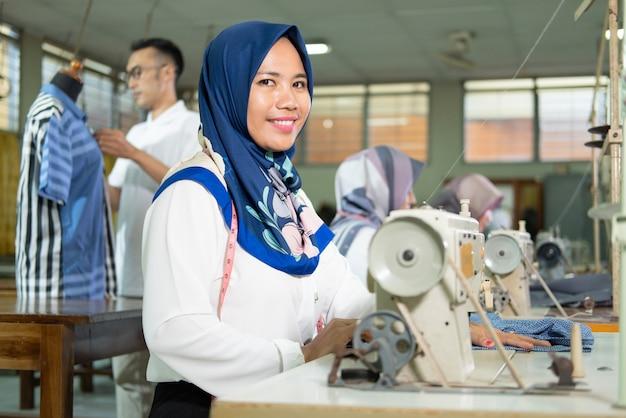 Alfaiate feminina em hijab sorri com uma fita métrica em volta do pescoço usando uma máquina de costura enquanto trabalha