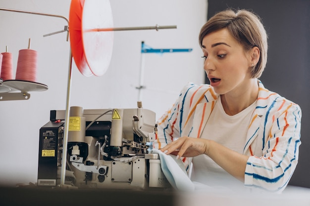 Alfaiate feminina trabalhando com máquina de costura