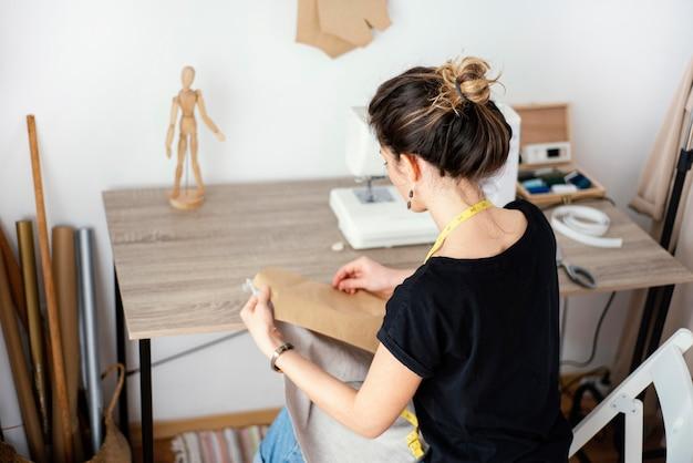 Alfaiate feminina trabalhando no estúdio de alto ângulo