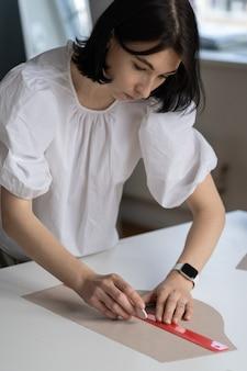 Alfaiate feminina usa régua para desenhar tecido padrão para cortar designer de materiais ou costureira no ateliê