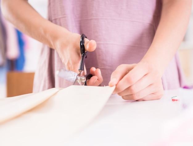 Alfaiate feminino cortando uma parte do pano com uma tesoura.