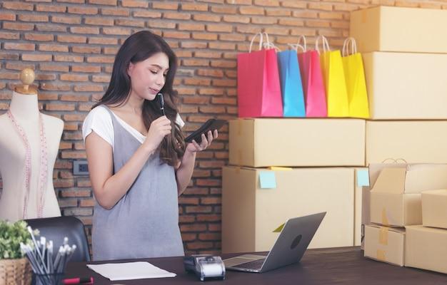 Alfaiate jovem com laptop está respondendo e-mails, sucesso empresarial de mulher de negócios. entrega de encomendas online de vendas