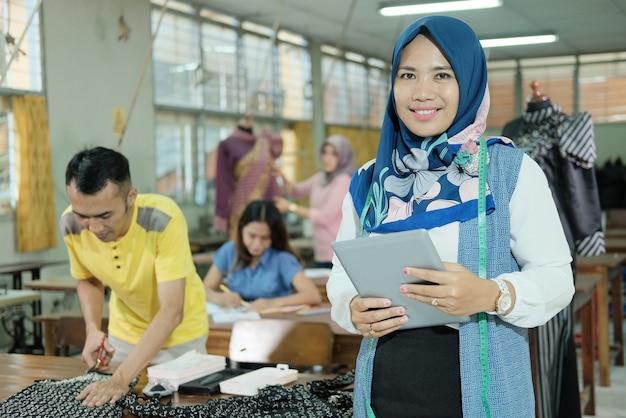 Alfaiate muçulmana em pé com véu e segurando um tablet na sala de produção de roupas
