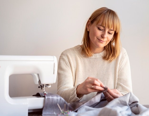 Alfaiate mulher usando agulha e linha para costurar