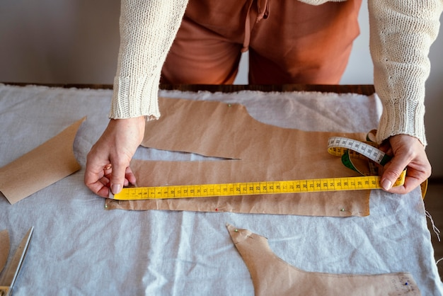 Alfaiate mulher usando régua para medir o tecido