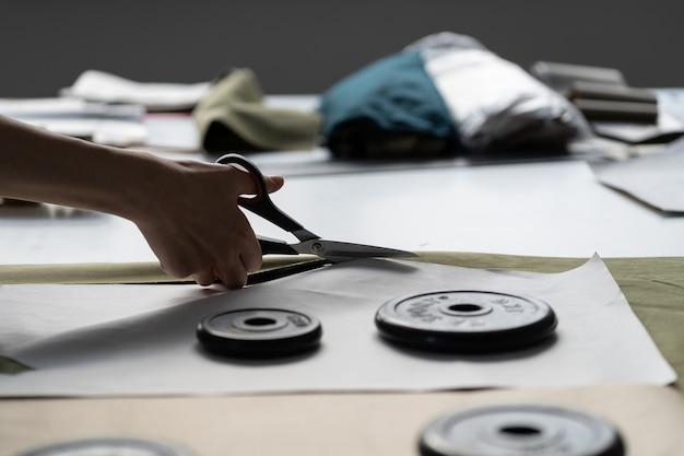 Alfaiate na loja do ateliê no trabalho, designer ou costureira segurando uma tesoura, corte um tecido na mesa