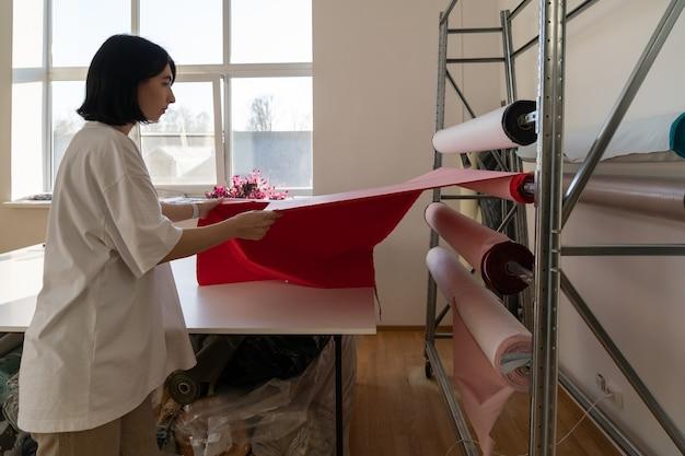 Alfaiate profissional feminina escolhe rolo de tecido para cortar material de medida de designer para rascunho de roupas