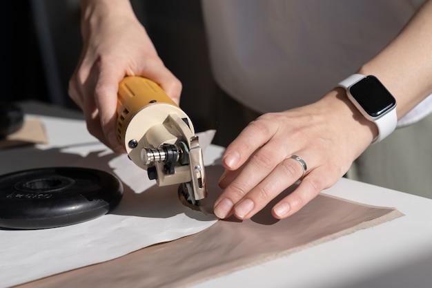 Alfaiate profissional usa cortador elétrico para cortar material de tecido para a nova coleção de roupas de design
